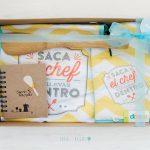 Caja decorada con delantal, recetario, manoplay cuchara de madera